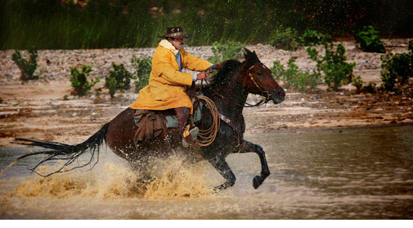 Myron Beck photo of cowboy on horse at gallop crossing a river