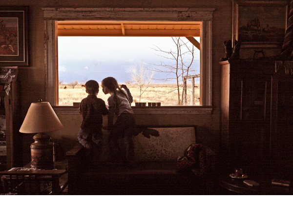 Nadine Levin photo of two children peering out of a ranch house window
