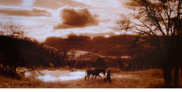 Myron Beck photo of a cowboy leading his horse past a pond