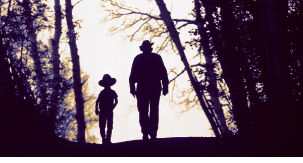 Beck photo of cowboy father and son walking through trees
