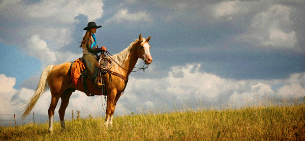 Cowgirl on a horse with a dramatic sky