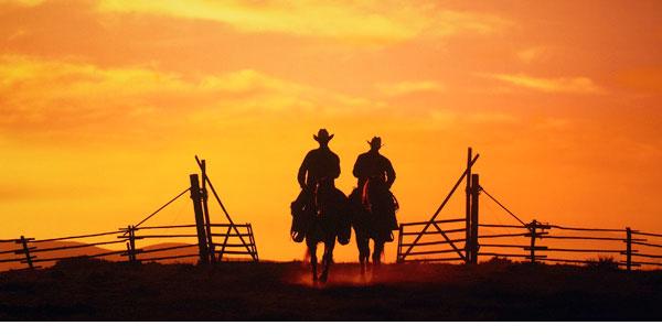 Myron Beck photo of 2 cowboys with beautiful orange sunset behind them